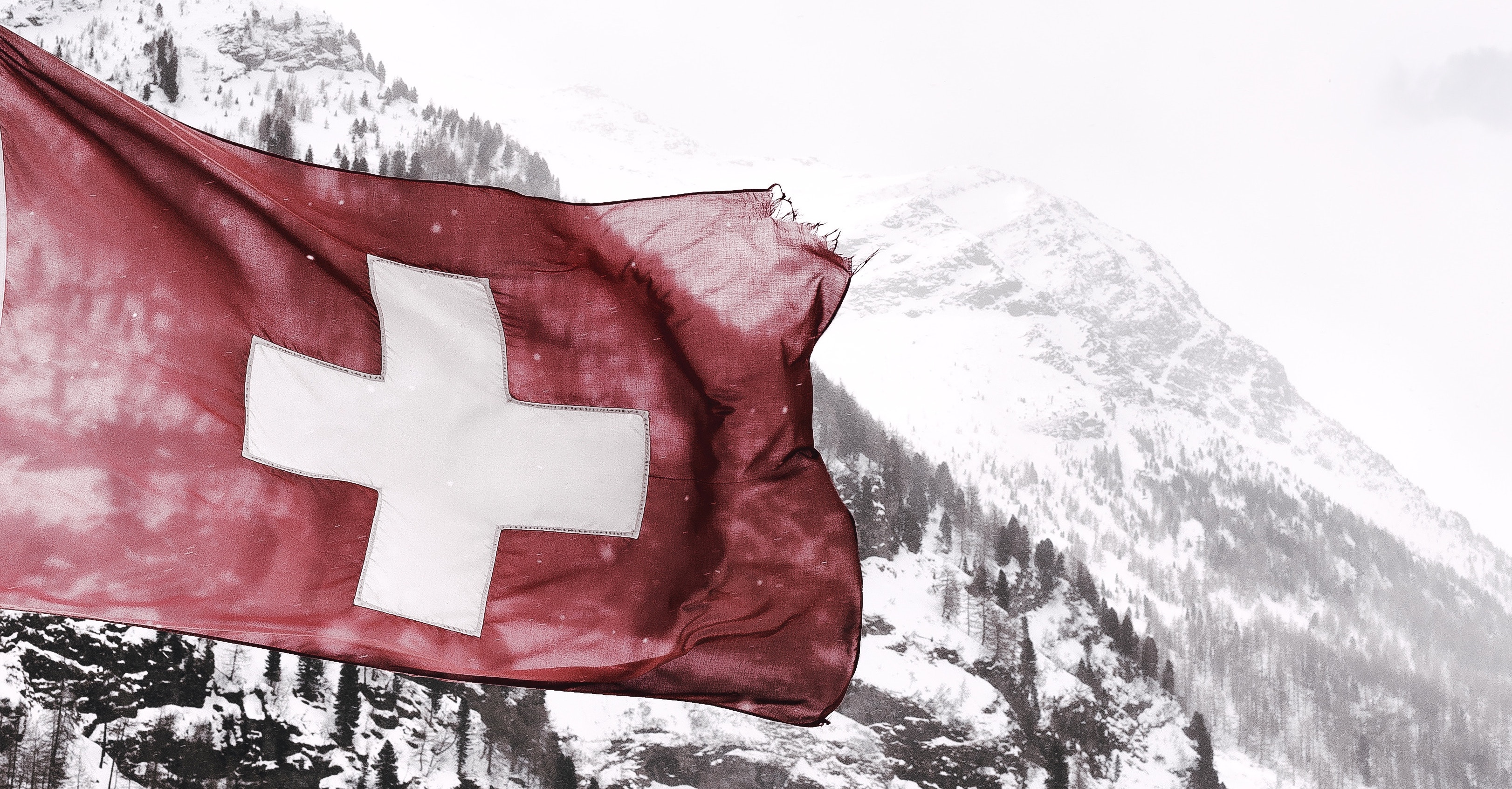 Swiss flag and snowy mountains