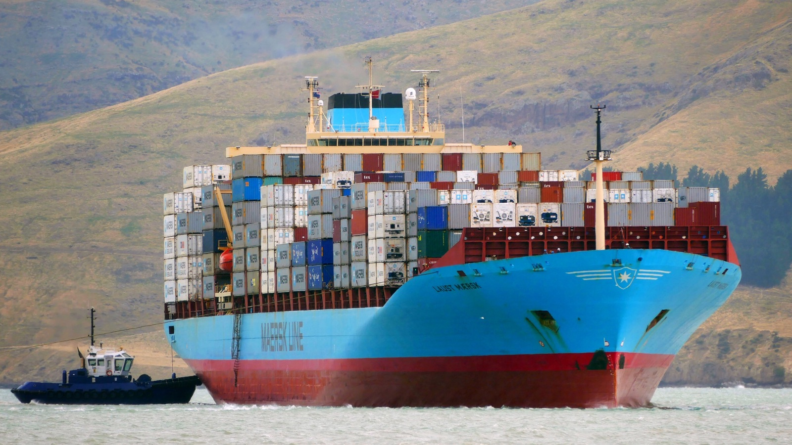 Maersk container ship pushed by a towboat