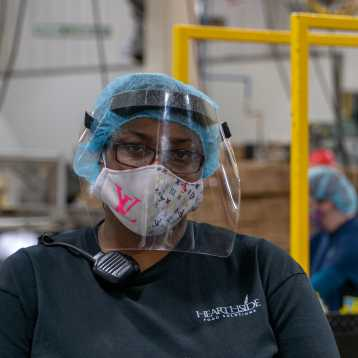 A woman wearing a mask and a Hearthside shirt.