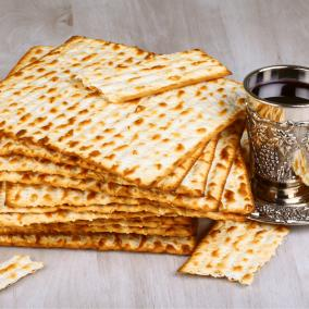 A tall stack of well-crisped unleavened crackers next to a silver goblet