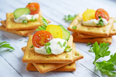 Stacks of savory crackers with tomatoes and sour cream on top.