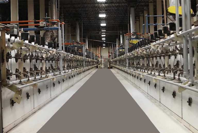 A long hallway filled with manufacturing equipment