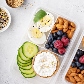 A refrigerated tray, packed to the brim with eggs, fruit, nuts, and cucumbers