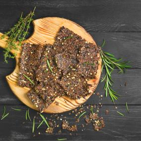 A wooden platter piled with deep-brown gluten-free crackers and crumbled herbs