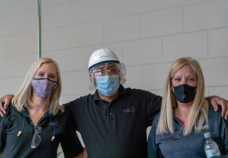 Three masked Hearthside workers stand side-by-side against a white wall.