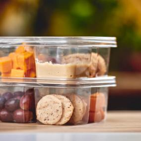 Cheese, dipping sauce, grapes, and crackers in clear plastic containers