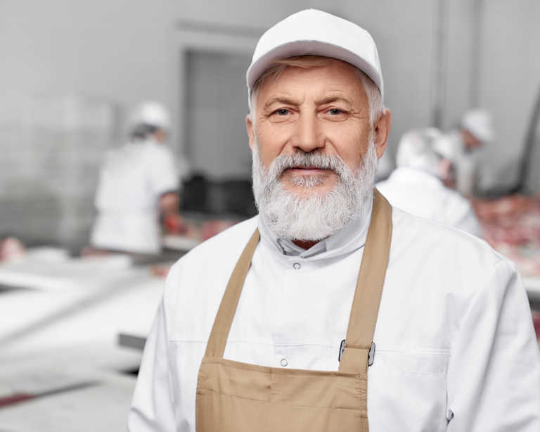 A bearded man with a white hat and beige apron smiles kindly at the camera