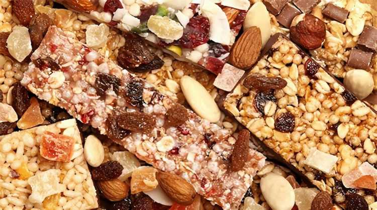 A pile of granola bars with various nuts and fruits.