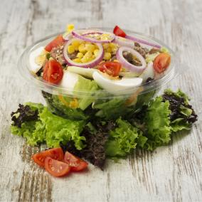 A cobb salad in a clear plastic bowl, on a wooden backdrop