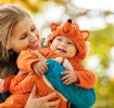 Mother holds baby in a fox baby carrier halloween costume