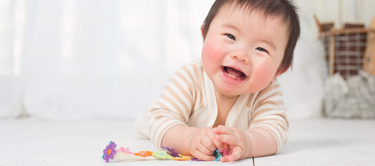 Baby smiling and playing with toy