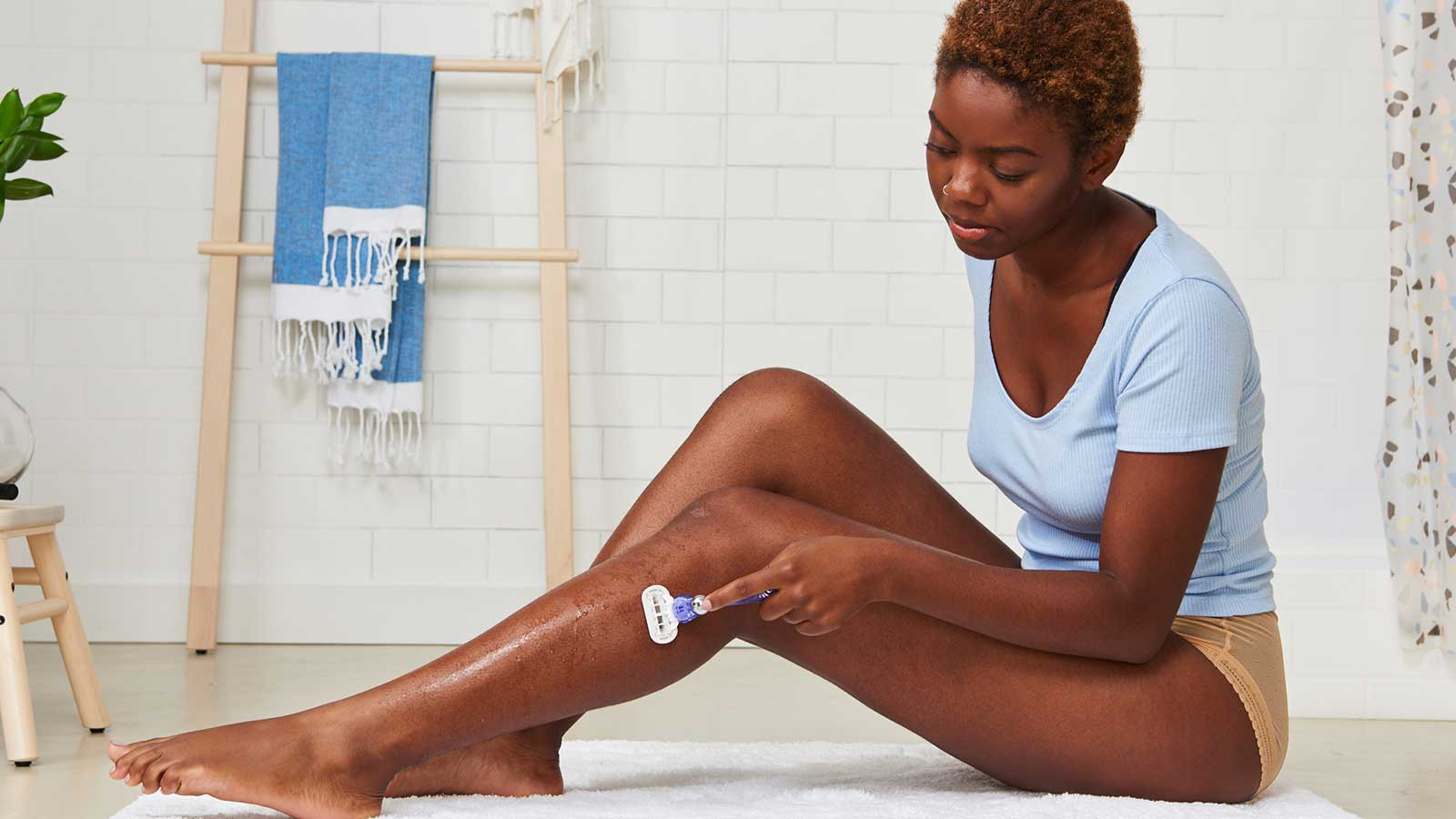 Woman Sitting on Bathroom Floor and Shaving Her Legs with Gillette Venus Razor