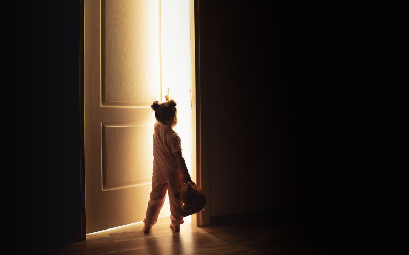 A small child holding a teddy bear opening a door.