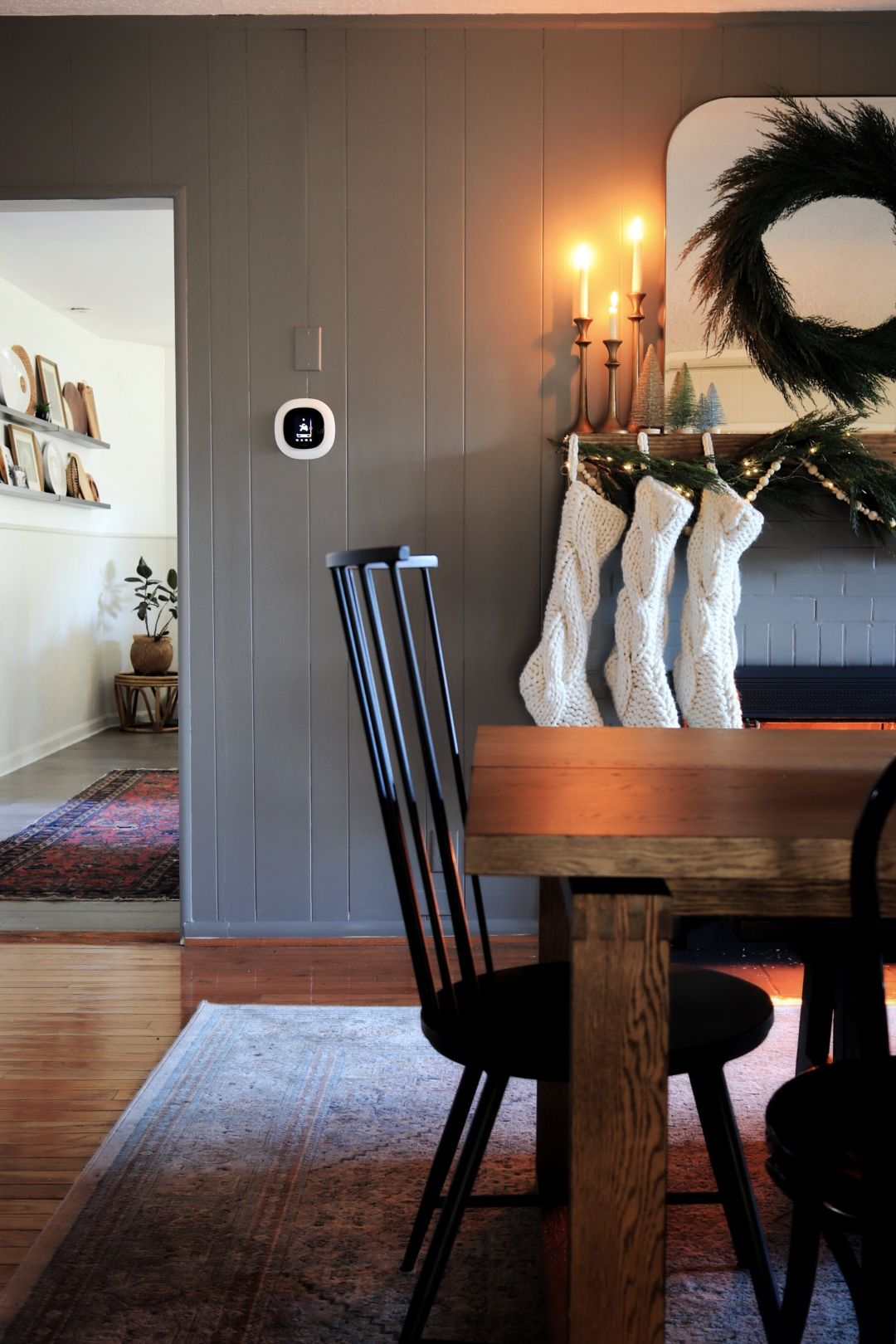 ecobee SmartThermostat with voice control on wall with wreath, stockings, and a fireplace beside it.