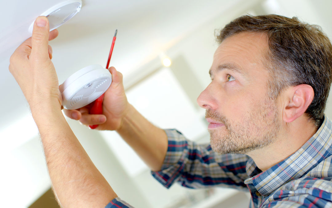 A man changes a fire alarm on a ceiling.