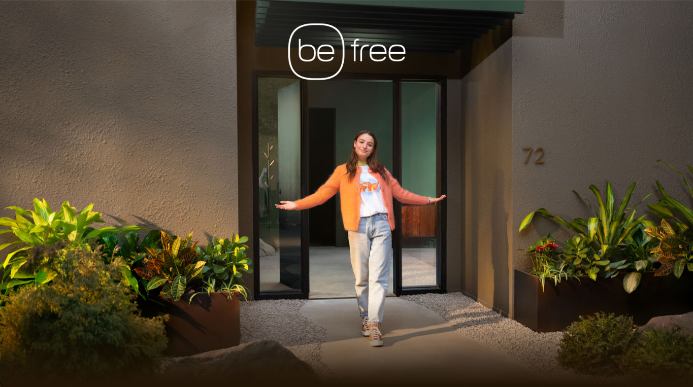 "A happy woman stands outside her house. The text ""be free"" is above her."