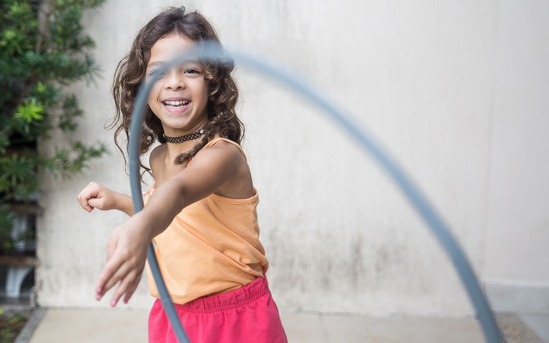 Child smiling while playing with hula hoop.