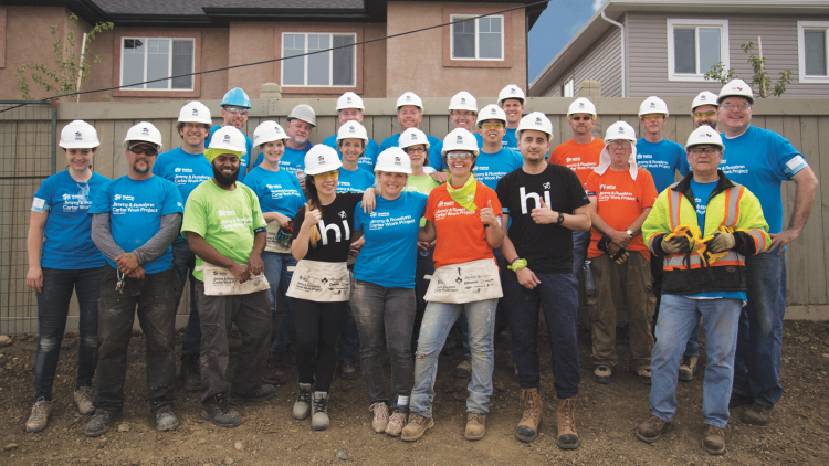 Group of volunteers, including ecobee employees, posing for a group picture while taking a break from building homes.