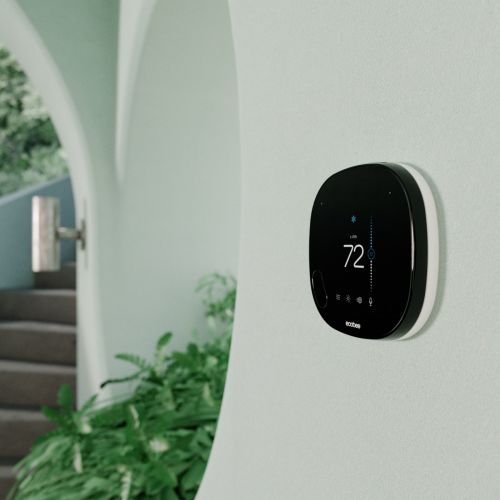 SmartThermostat with Voice mounted on wall, with plants in the background