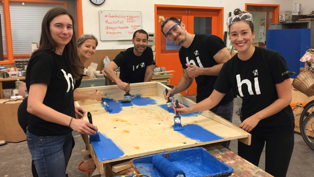 "Five ecobee employees wearing ecobee ""Hi"" t-shirts painting a wooden accessibility ramp the colour blue"