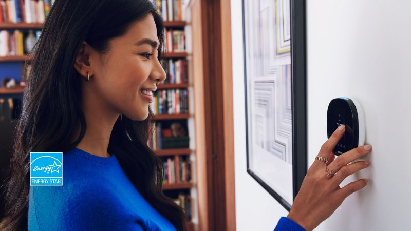 Lady in blue shirt using her ecobee thermostat's touchscreen