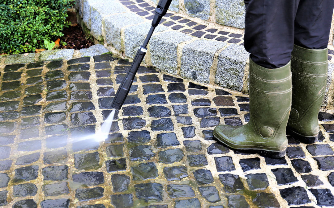 A person uses a pressure washer on an outdoor stone floor.