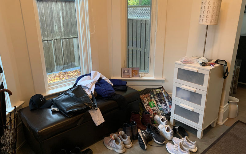Entranceway cluttered with shoes, bags, and other nicknacks.