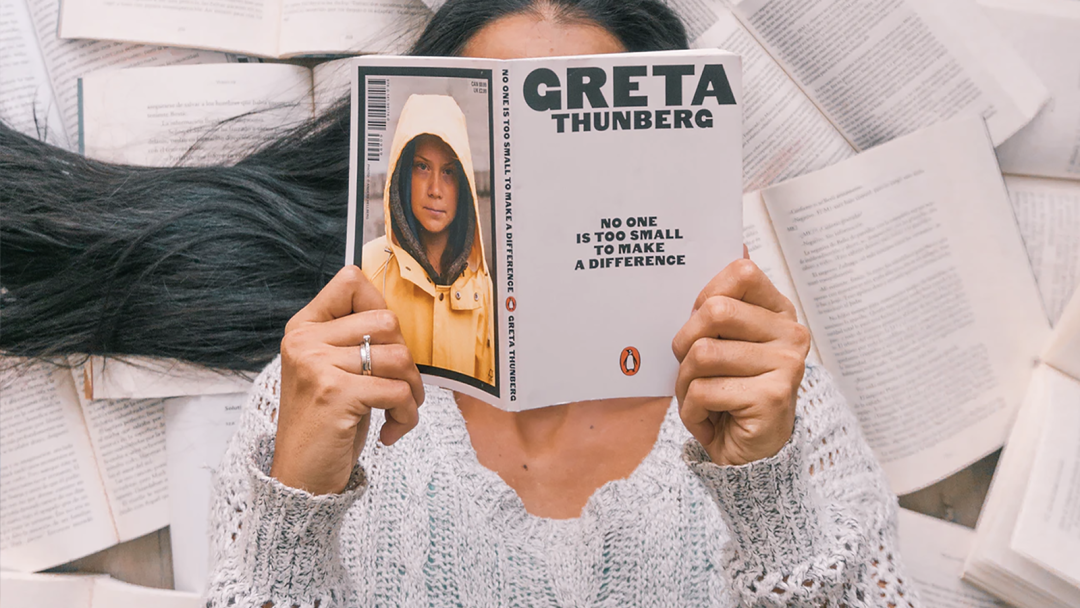"A woman laying on a pile of open books reads Greta Thunberg's ""No One is Too Small to Make a Difference"""