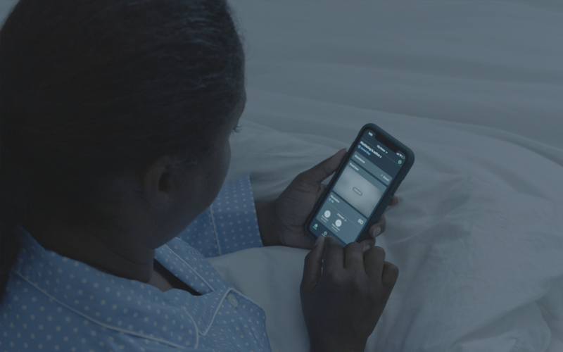 Lady sets the temperature from bed with the ecobee app.