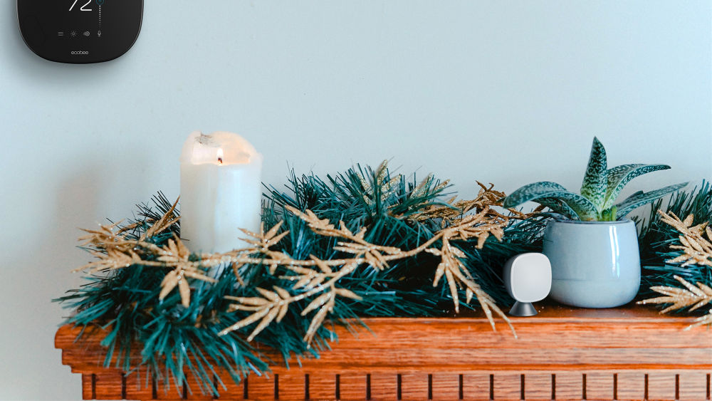Fireplace mantel with festive garland, candle, and plant. An ecobee thermostat and SmartSensor complete the picture.