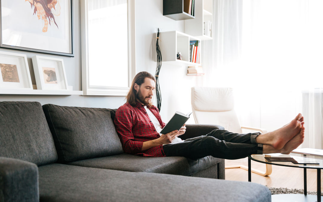 Man in unbuttoned red plaid shirt with white tee-shirt reading on couch.