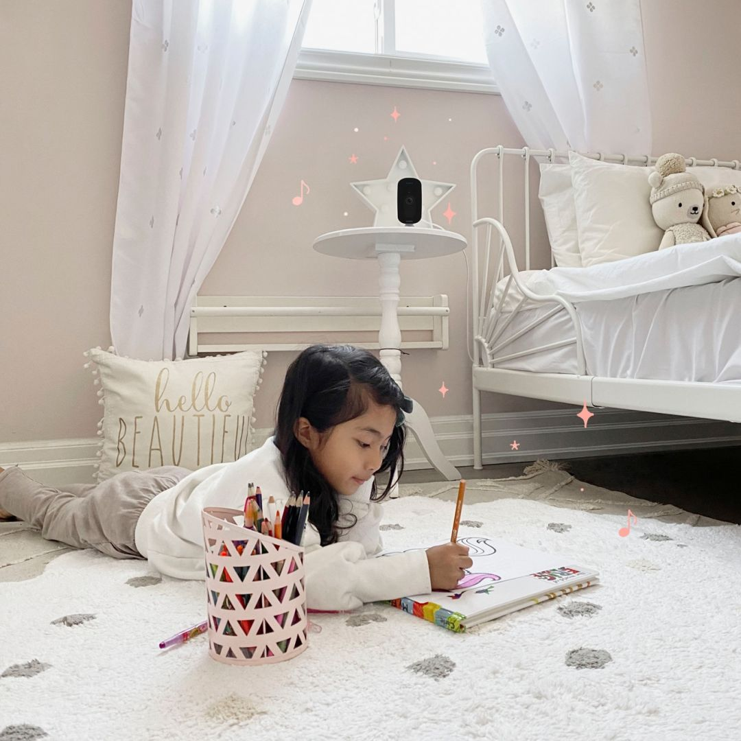 A little girl plays in her room while the ecobee SmartCamera watches from a table.