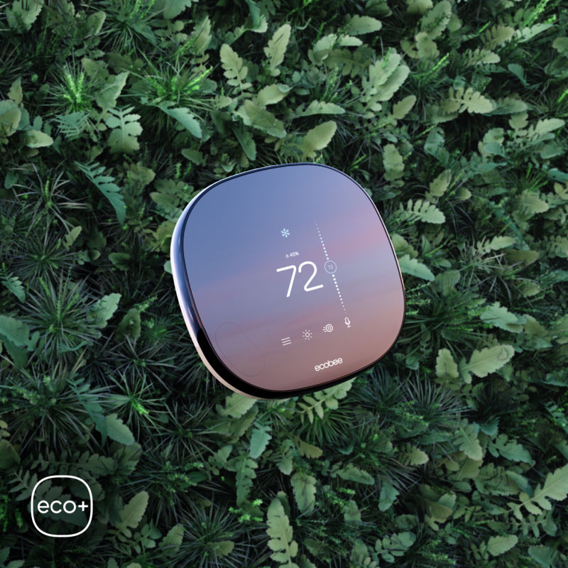 SmartThermostat with voice control laying on lush, verdant backdrop symbolizing ecobee's commitment to sustainable living through technology.