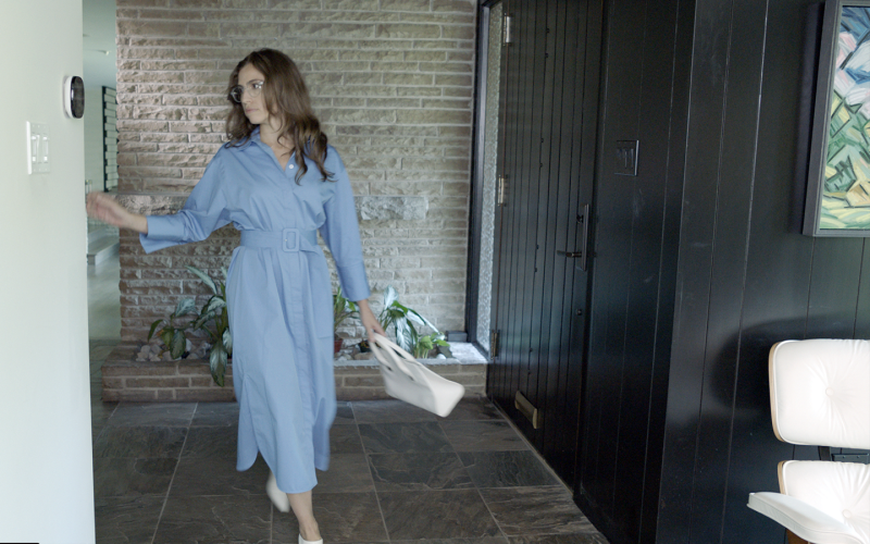 Lady with long brown hair in blue outfit and purse arrives back to a comfortable home. The occupancy-sensing and geofencing abilities of modern smart thermostats help shift between power savings and comfort modes automatically.