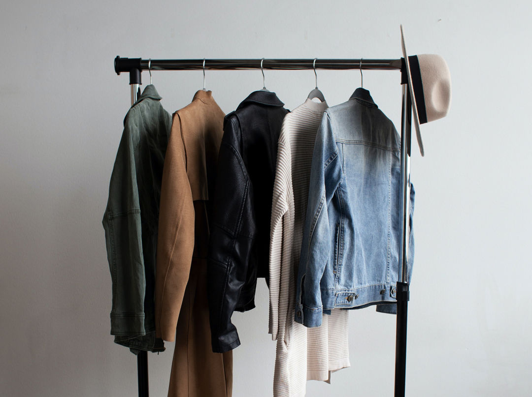 A clothing rail with five jackets and a hat.