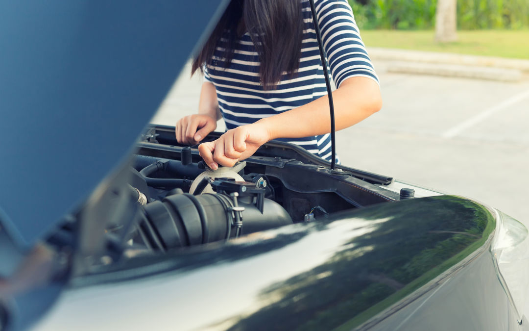A woman checks her car's oil.