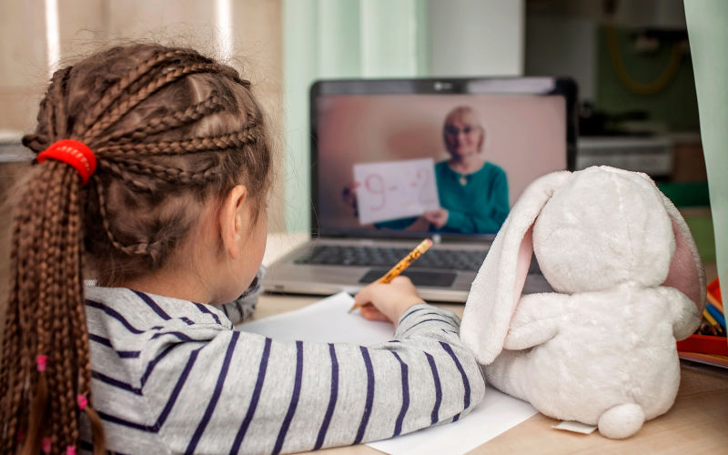 A child watches a teacher on a laptop screen.
