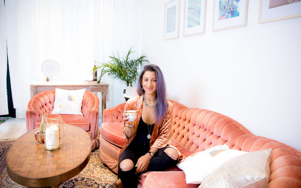 Vanessa Vakharia, the founder and director of The Math Guru sitting on a vintage salmon-colored chesterfield sipping tea at home in midtown Toronto. Vanessa shared her thoughts with us on creating a tranquil co-working space for parents and kids.