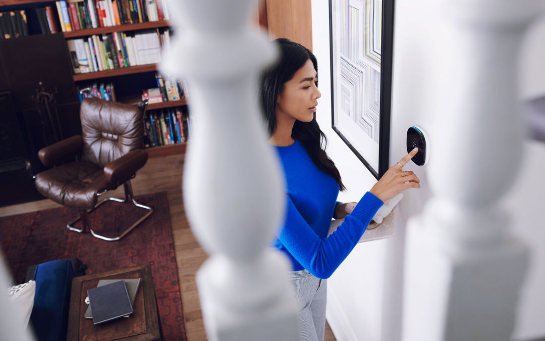 Woman in blue shirt sets household temperature with ecobee smart thermostat.