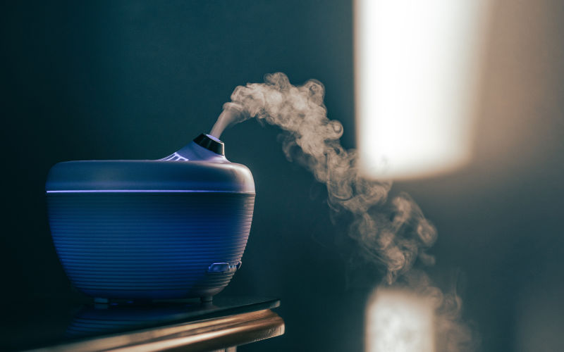 A blue humidifier on table releasing water vapor.