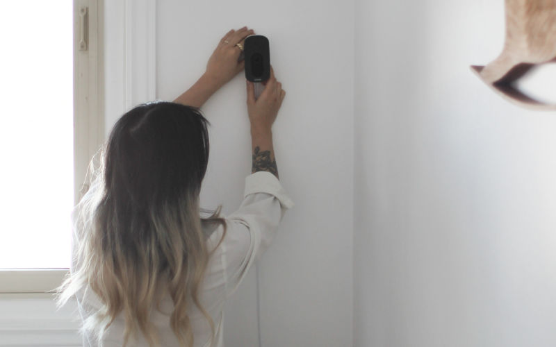 A woman sets up an ecobee SmartCamera on her wall.