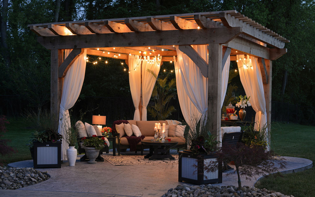 A backyard gazebo with lights and comfy seating at dusk.