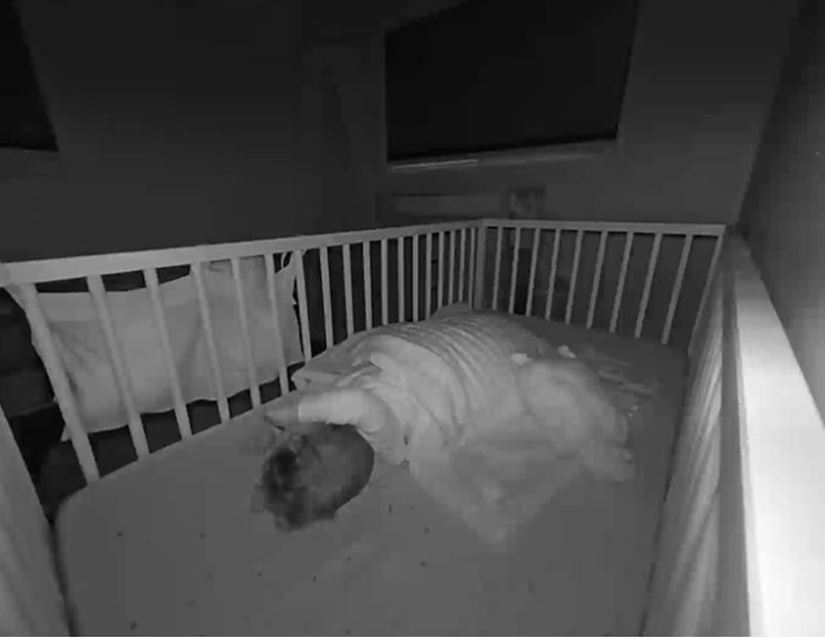 A nightmode view of a baby asleep in a crib.