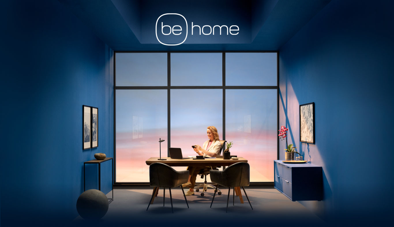 "A woman sits looks at her phone while sitting in an office. Text saying ""be home"" floats above her."