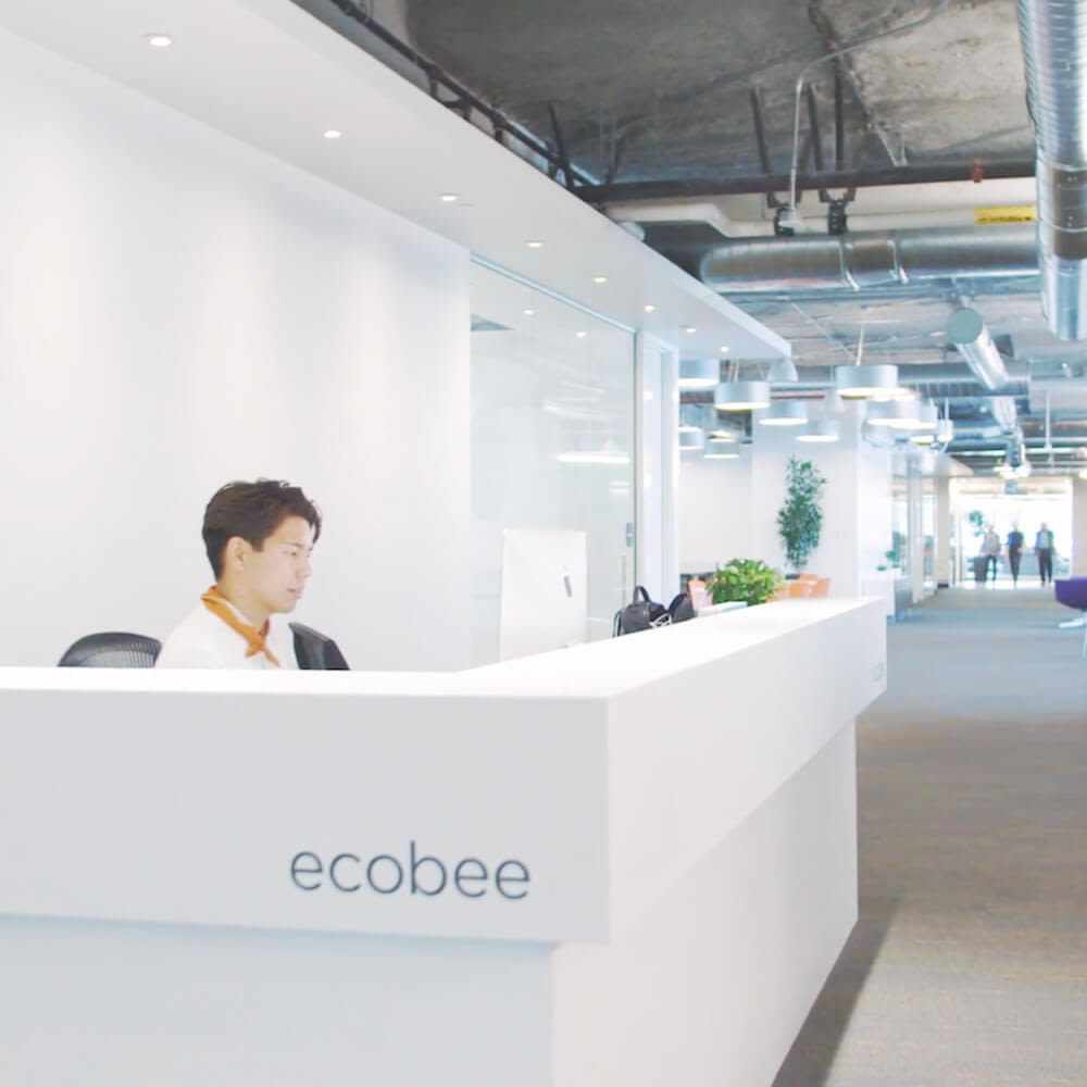 Man sitting behind welcome desk at ecobee headquarters.