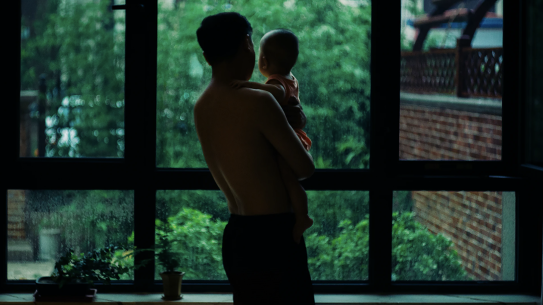 A man holding a baby looks out a window onto a forest.