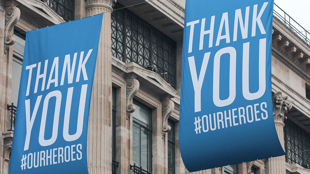 "Large blue banners saying ""Thank you #ourheroes"" hang outdoors."