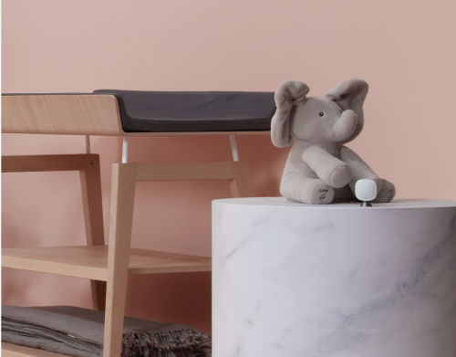 A stuffed elephant toy sits next to a changing table in a baby's room.