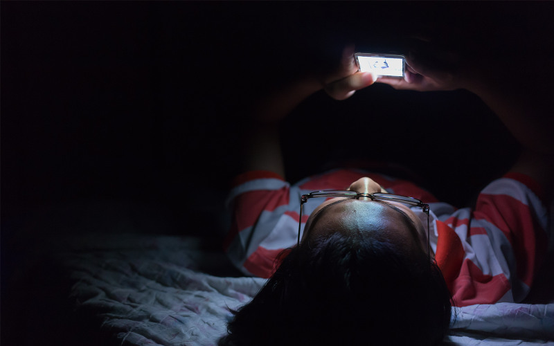 Boy using iPhone in bed at night. Just like an iPhone, pictured laying on table, the data created by ecobee thermostats is encrypted to protect your privacy.