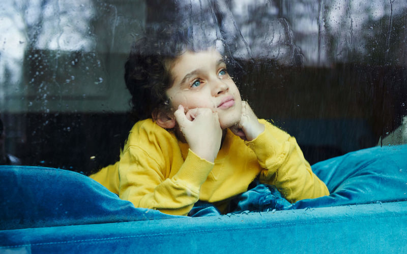Boy on couch gazes out window on rainy day.
